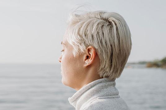 Femme sereine sur le bord de l'eau, visage vers le soleil matinal