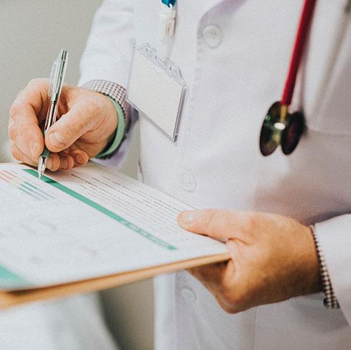 Gros plan d'un médecin qui prend des notes sur un pad